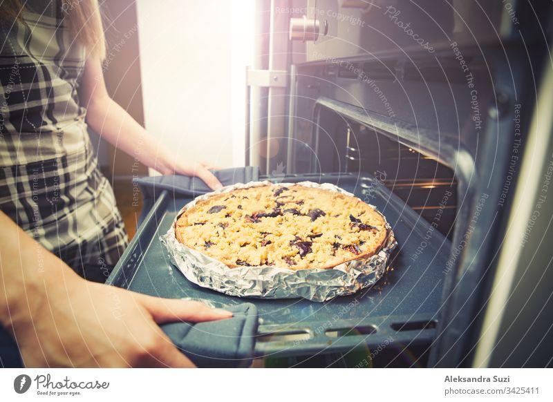 Frauenhände beim Herausnehmen des Tabletts mit Gebäck aus dem Ofen, Nahaufnahme. Frischer hausgemachter köstlicher Pflaumenkuchen. backen Kuchen Koch