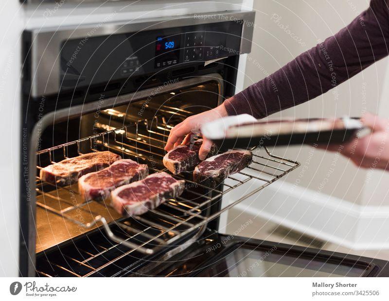 Mann schiebt Steaks in den Ofen rohes Steak Rindfleisch rohes Rindfleisch Essen zubereiten Kochsteak Mann kocht Kochen von Steaks im Ofen rotes Fleisch