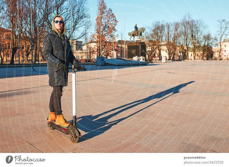 Junger Mann fährt einen Elektroroller auf der Straße in der Innenstadt, der über ein Smartphone gemietet wird. Aufgeschlossene Menschen, reale Momente, authentische Situation