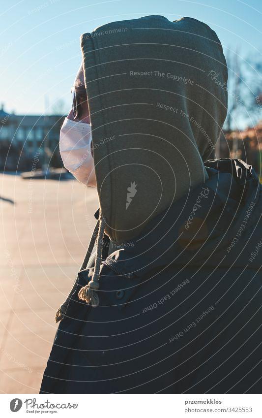 Junger Mann mit Kapuze, der die Gesichtsmaske trägt, um eine Virusinfektion zu vermeiden und die Ausbreitung der Krankheit zu verhindern. Spaziergang im Stadtzentrum. Schutz vor einer Virusinfektion. Echte Menschen, authentische Situationen