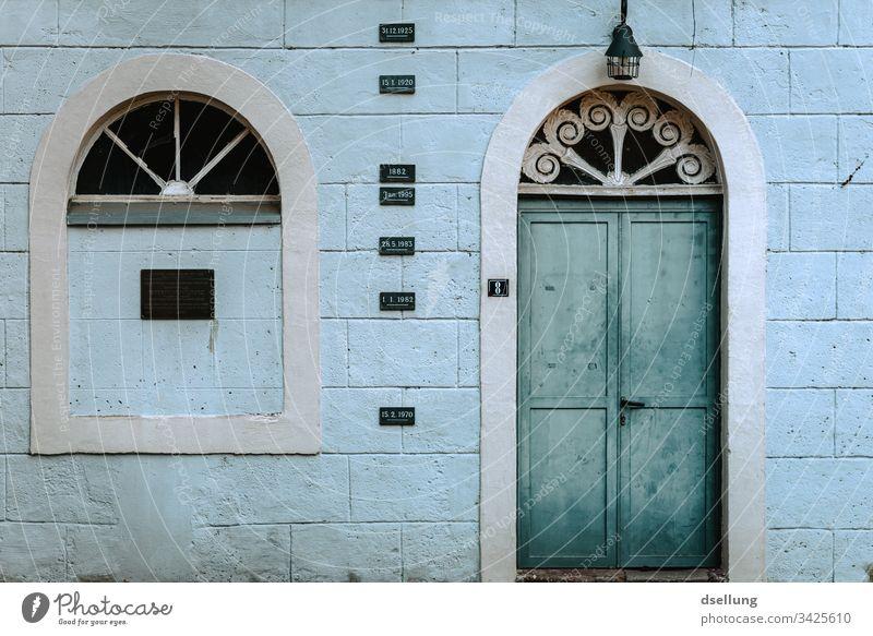 Verwitterte Fassade mit türkiser Tür Haus Fenster Ordnung Menschenleer Architektur Außenaufnahme abstrakt ästhetisch Gebäude Farbfoto Tag grau trashig Wand