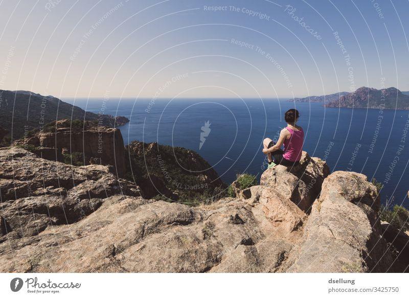 eine Frau genießt nach einem Wandertrip die erreichte Aussicht auf Meer und Felsen in der Sonne Sonnenstrahlen entfernung Blick schön Wellness entdecken hell