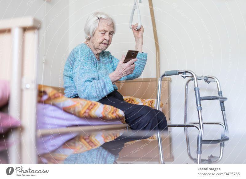 Ältere 96 Jahre alte Frau, die eine Telefonnachricht liest, während sie auf einem medizinischen Bett sitzt und von einem Halter gestützt wird. Senior heimwärts