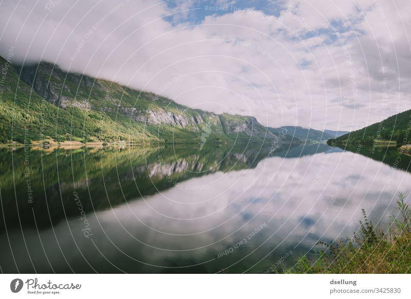 Spiegelglatter See mit grünen Bergen am Ufer Wellness Felsen Zeit für sich Expedition Pause Camping Erde Klimawandel harmonisch Kontrast Urelemente Wohlgefühl