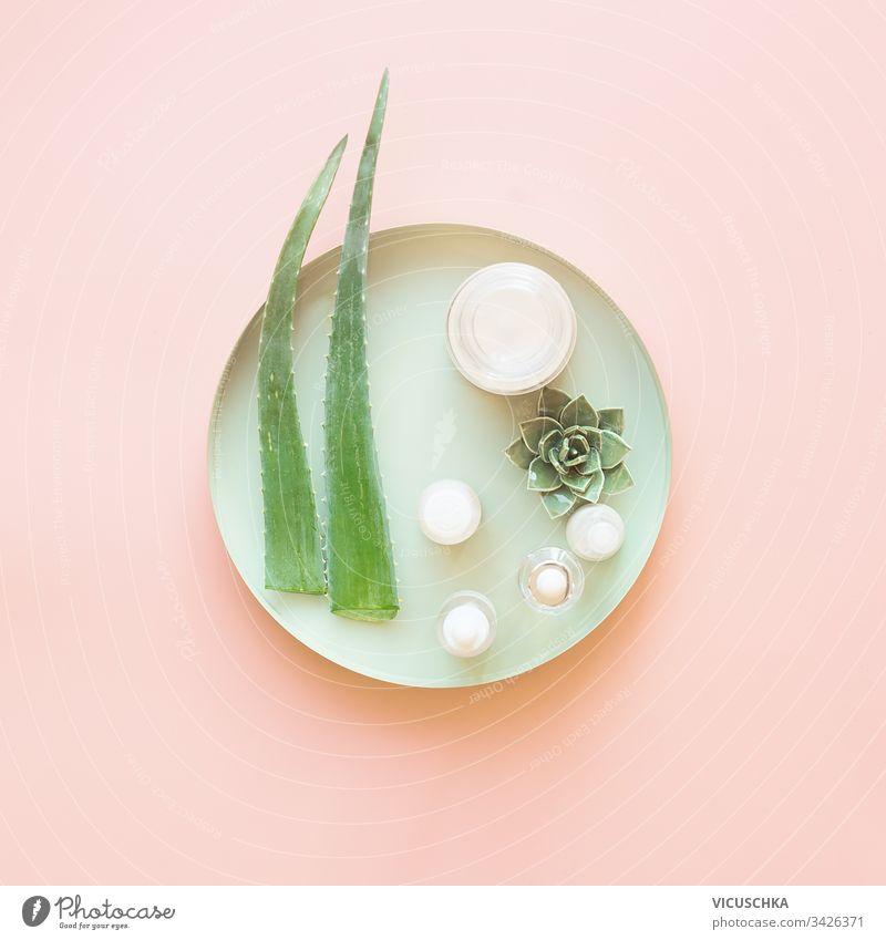 Moderne feuchtigkeitsspendende Kosmetikprodukte mit frischen Aloe Vera-Blättern auf hellgrünem Tablett auf pastellrosaem Hintergrund. Ansicht von oben. Moderne Gesichtshautpflege. Schönheitskonzept. Gestaltung
