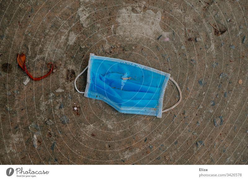 Gebrauchter dreckiger blauer einweg Mundschutz gegen Viren, Corona und Covid-19 der weggeworfen auf dem Boden liegt Einweg Müll Coronavirus Schutz Virus