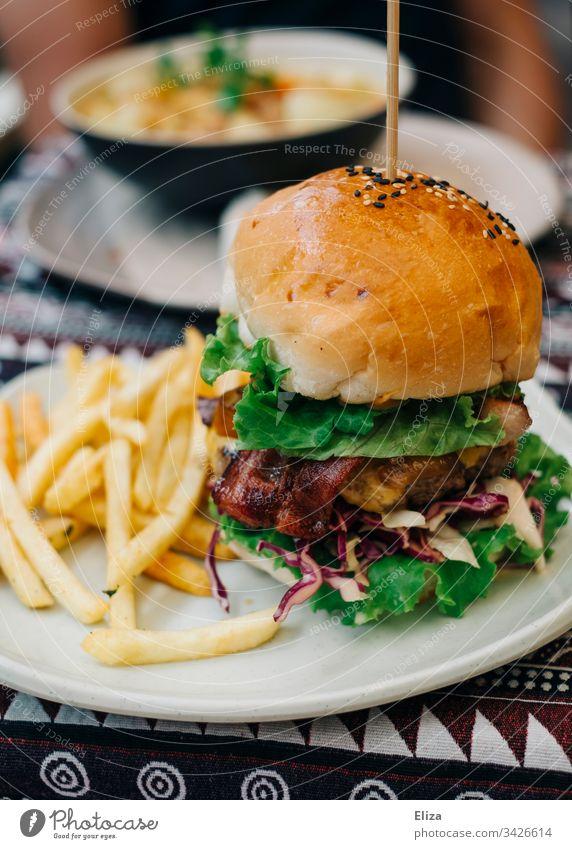 Ein leckerer Burger mit Pommes auf einem Teller; Fastfood Hamburger Fast Food Restaurant frich Mittagessen Mahlzeit Essen frisch Lebensmittel ungesund Fleisch