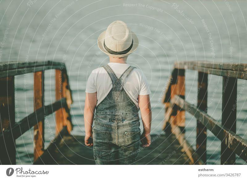 Rückansicht eines nachdenklichen Kindes, das auf das Meer schaut Kindheit nostalgisch Gedanke Einsamkeit einsam Ausdruck Freiheit Unschuld Porträt ernst träumen
