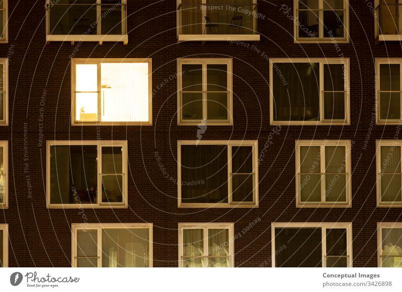 Einfach beleuchtete Fenster in einem modernen Wohnblock betätigen Appartement Anfänge Gebäude Leben in der Stadt Konzepte Kondominium heimisch früh elektrisch