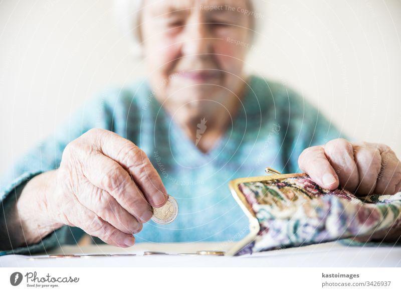 Besorgte ältere Frau sitzt am Tisch und zählt Geld in ihrer Brieftasche. Senior Rentnerin Armut Ruhestand alt leer Münzen Hintergrund unglücklich pleite einsam