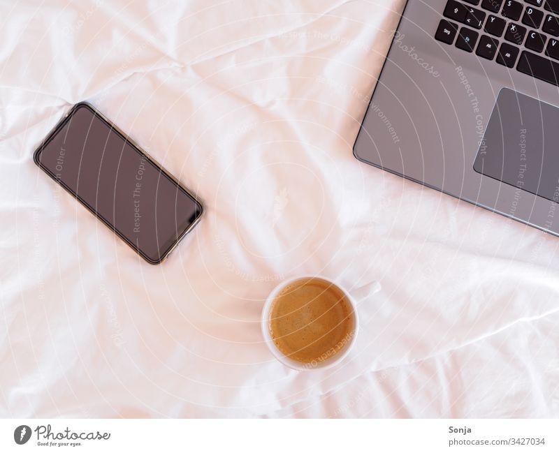 Laptop, Smartphone und eine Tasse Kaffee auf einer weißen Bettdecke, Heimbüro Heimarbeitsplatz Technik & Technologie Lifestyle Computer Business Internet