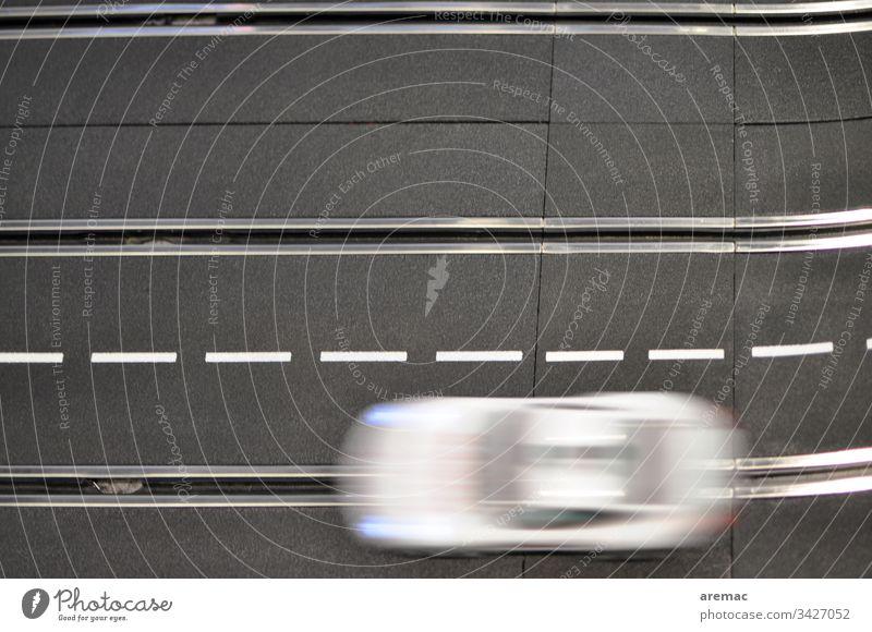 Verwischtes Auto auf einer Modellrennbahn Automobil Rennbahn Carrera Bewegung schwarz weiß Spur Elektro elektrisch Spielzeug Geschwindigkeit Rennwagen