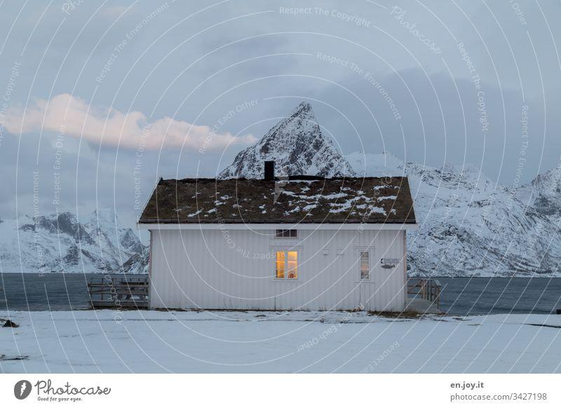 """Kleines weißes Haus am Fjord vor schneebedeckten Bergen Sakrisoy Lofoten,"""" Lofoten Inseln Reisefotografie Einfamilienhaus Idylle Ferienhaus Rorbuer Reinefjorden"""