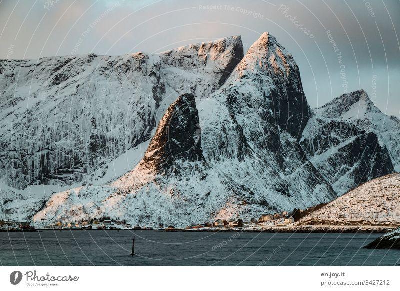 """Fischerdorf am Fjord vor verschneitem Berg Sakrisoy Lofoten,"""" Lofoten Inseln Reisefotografie Idylle Reinefjorden Wasser Tourismus Meereslandschaft"""