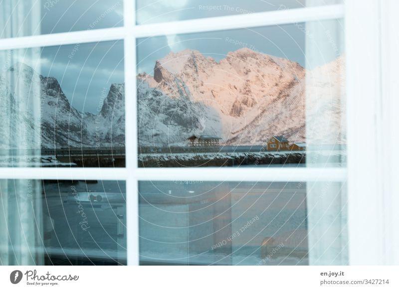 Kleines gelbes Haus am Fjord vor schneebedeckten Bergen spiegelt sich in Fensterscheibe Norden Erholung Winterurlaub Schnee Zentralperspektive Umwelt