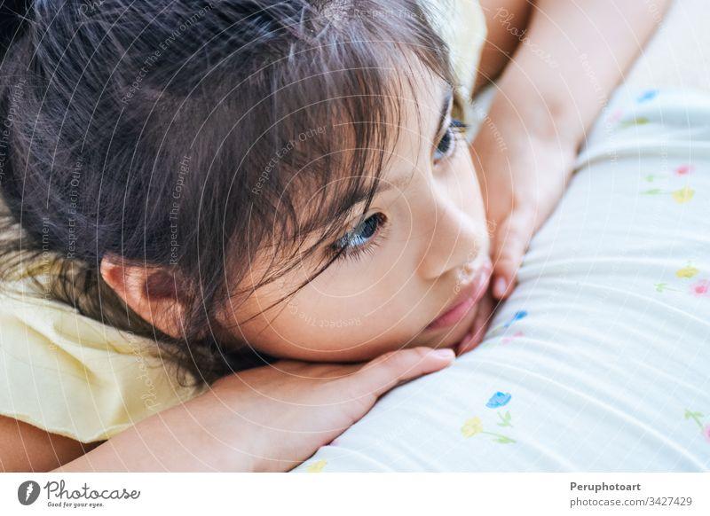 Ein liebenswertes Mädchen, das im Bett denkt, oder sie könnte auch traurig sein. Kind Denken Person Kindheit Porträt hübsch niedlich wenig klein schön Baby weiß