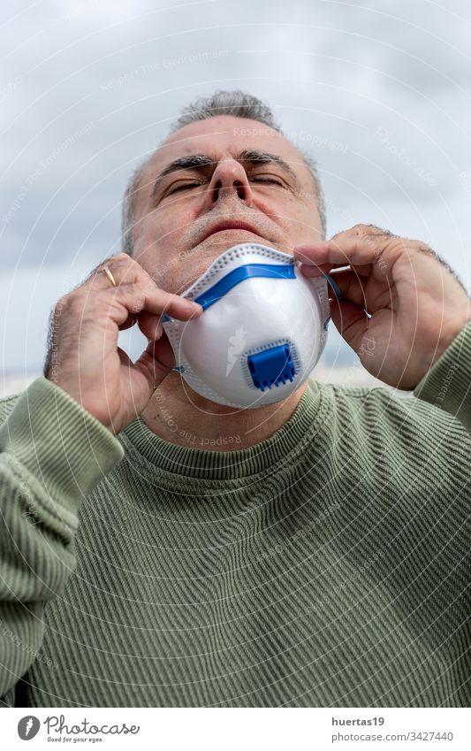 Erwachsener Mann mit Schutzmaske für Coronavirus medizinisch Mundschutz Seuche schützend Infektion Virus covid-19 Gesundheit Thermometer Grippe Gesicht Pandemie