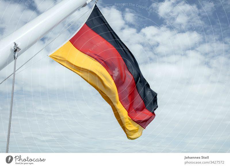 Deutschlandfahne im Wind Fahne Flagge Schwarz Rot gold Stoff Schiff Fahnenmast Seil Himmel Wolke Feiertag Feierlichkeit Stolz Nation Gesellschaft Einheit