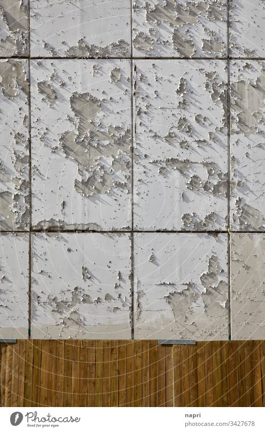 Der Lack ist ab | Wandfarbe an einer Fassade blättert großflächig ab, Bauzaun aus Holz davor. Putz marode abblättern Ostalgie Baustelle verwittert Farbe weiß