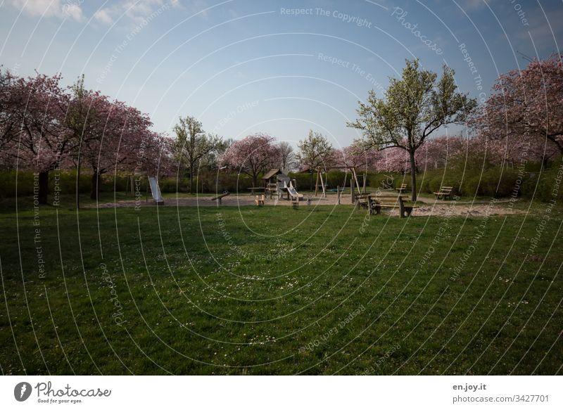 Corona thougths | leerer Spielplatz mit grüner Wiese und blühenden Bäumen Rasen Bank Parkbank Rutschbahn Schaukel blühende Bäume Gänseblümchen Ausgangssperre