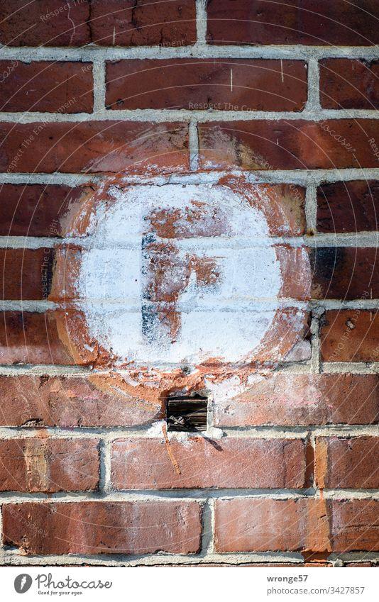 Großes rotes F für Hinweis auf den Feuerlöscher auf weißem Grund an einer Backsteinmauer Buchstaben Farbfoto Tag Schriftzeichen Außenaufnahme Großbuchstabe