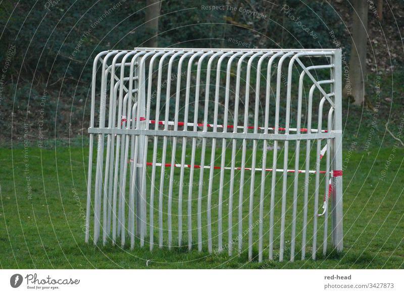 Metallfussballtor von hinten auf dem Fussballfeld, das wegen Corona mit einem Flatterband geschlossen wurde Fußballtor gesperrt grün Spielplatz Fußballfeld Tor