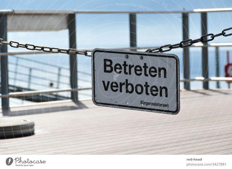 Betreten Verboten - Schild an Gliederkette vor Bootsanlegestelle, im Hintergrund Geländer, hellblauer Himmel und See Betreten verboten Schilder & Markierungen