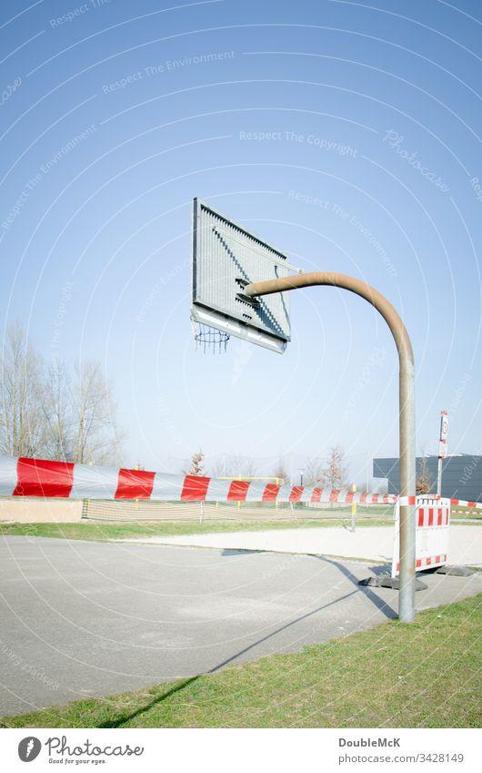 Spielen verboten - menschenleerer Basketballplatz gesperrrt auf Grund des Coronavirus Absperrung Absperrband Sperrung Basketballkorb Tag Außenaufnahme Farbfoto