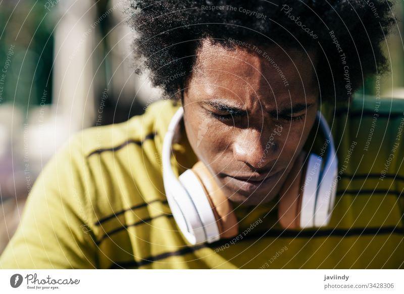 Nahaufnahme eines ernsthaften schwarzen Mannes, der nach unten schaut. Afro-Look betroffen nachdenklich besinnlich Behaarung Afrikanisch männlich Gesicht