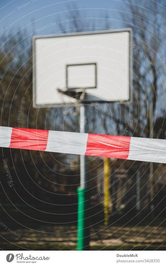 Spielen verboten - Basketballplatz gesperrrt auf Grund des Coronavirus Absperrung Absperrband Sperrung Basketballkorb Tag Außenaufnahme Farbfoto Menschenleer