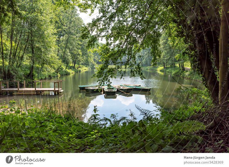 Ruderboote auf einem Bergsee mit Holzsteg in einem bewaldeten Tal bergsee gebirgssee Teich wasser Weiher Boot naherholungsgebiet ruhig entspannung brün nass