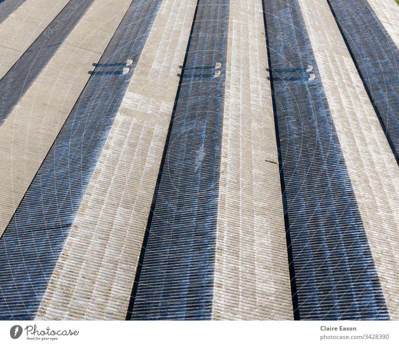 Luftaufnahme des Nordlicht-Fabrikdaches, das den gesamten Rahmen ausfüllt, mit drei Paaren kleiner Schornsteine. Dach Nordlicht-Dach grafische lineare Schatten