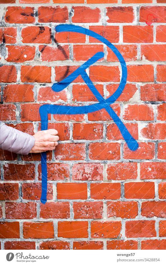 Eine Frauenhand hält scheinbar einen Hammer und eine Sichel - Graffito vor roter Backsteinwand Graffiti Hand hammer und sichel Backsteinmauer Hochformat