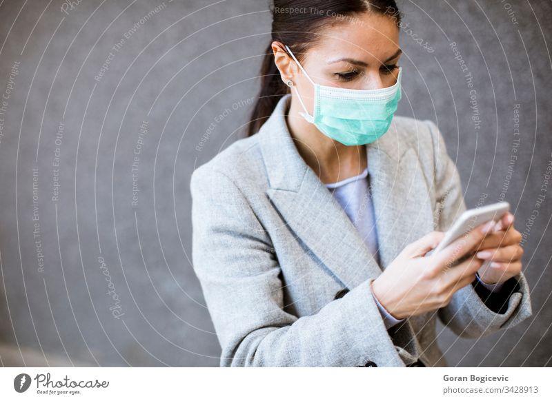 Hübsche junge Frau mit schützender Gesichtsmaske auf der Strasse Virus Mundschutz Gesundheit ansteckend Sicherheit Seuche Telefon Krankheit Mobile Coronavirus