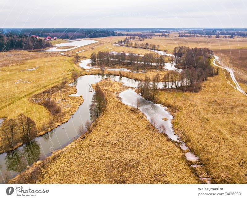 Kleiner Fluss mit ausgetrockneten Bäumen ohne Blätter im Winter / Anfang Frühling - Luftaufnahme. Launisches, bedecktes Wetter Bach strömen Straße Wegbiegung