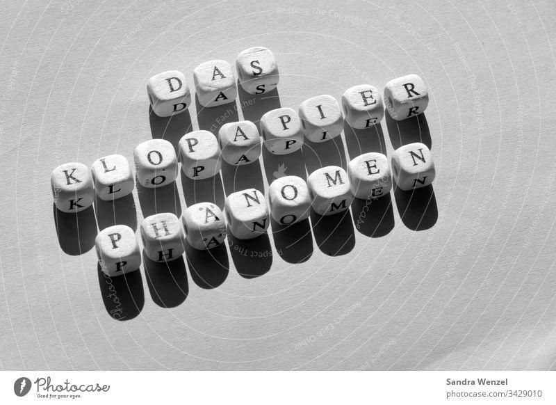 Würfel mit Buchstaben, das Klopapier Phänomen Konsum Krieg Überfluss Knappheit Corona Krise Medien Virus Kaufverhalten Hamsterkäufe Politik Wirtschaft