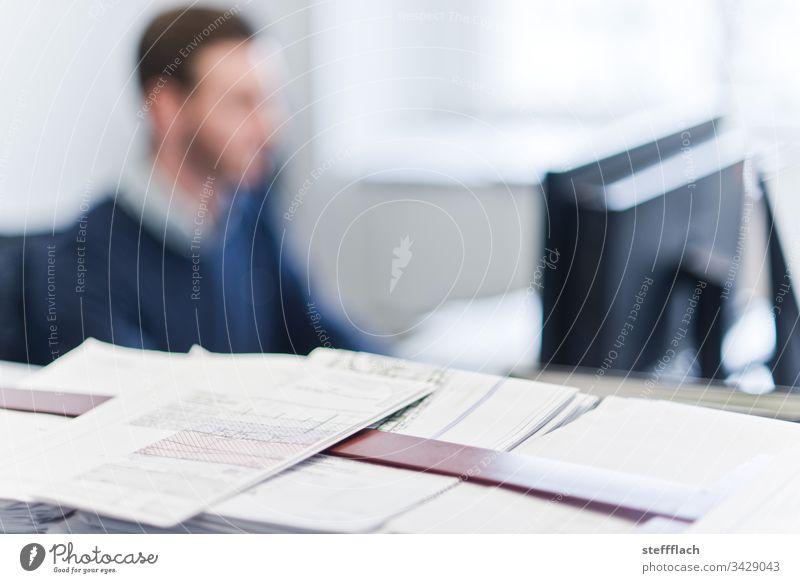 Architekten Arbeitsmaterial im Vordergrund, im Hintergrund unscharf ein Mitarbeiter vor dem Monitor Laptop Menschen Büro Office Telko Tisch Arbeitsplatz