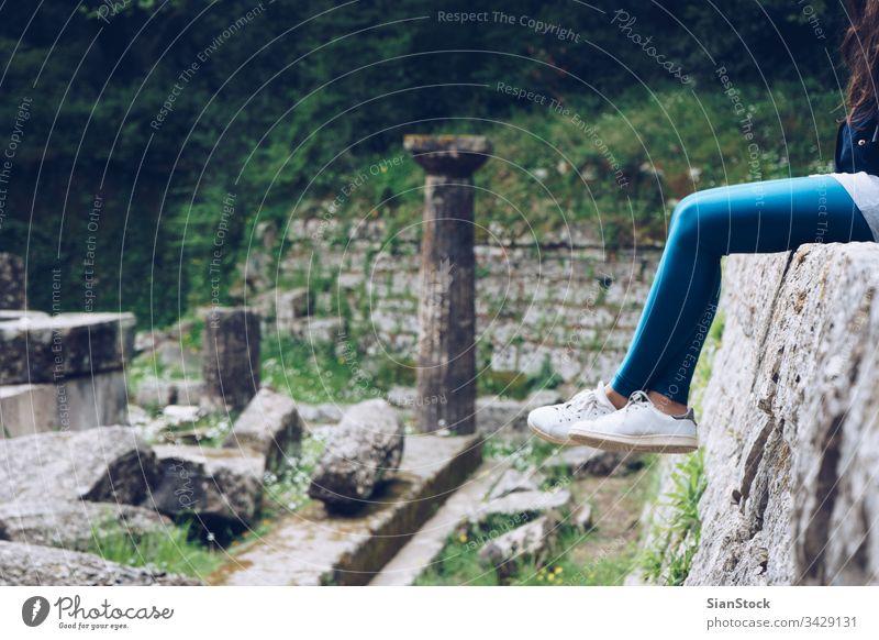 Mädchen sitzt auf Überresten eines dorischen Tempels, Mon Repos-Park, Korfu-Stadt, Griechenland Palast repo repos kerkira Insel Gebäude Wahrzeichen historisch