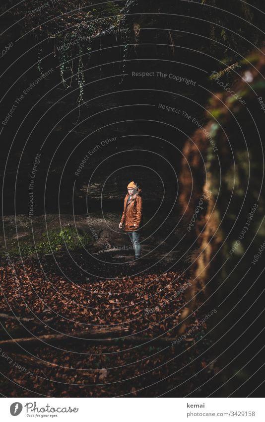 Frau in einer Schlucht im Wald, schaut in Kamera mystisch Naturmystik geheimnisvoll Tag braun natürlich grün Stein Mensch schauen Laub düster dunkel stehen