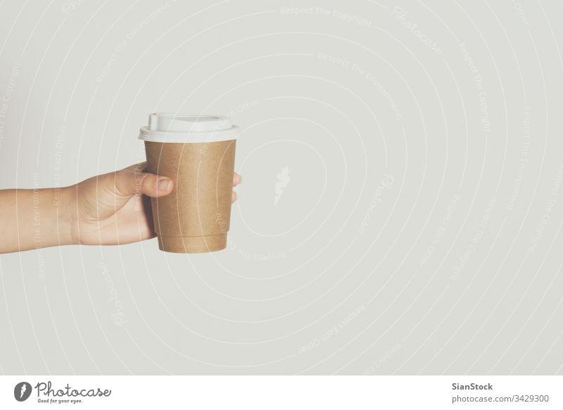 Frauen halten in der Hand eine braune Papiertasse mit heißem Kaffee. Tasse vereinzelt weiß trinken Hintergrund Einwegartikel Café Deckel Container Koffein