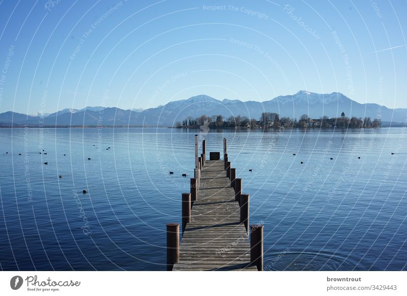 Bootssteg am Chiemsee mit Blick auf die Fraueninsel. Steg See Wasser Holz blau Alpen Insel Berge u. Gebirge Blauer Himmel Gstadt Außenaufnahme Natur Landschaft