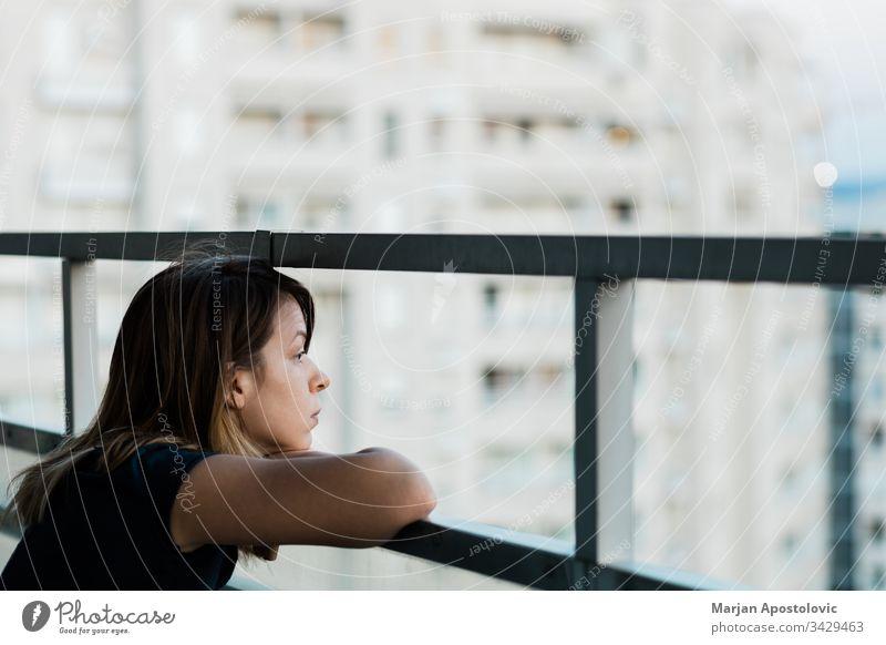Junge traurige Frau, die durch den Balkon eines Wohnhauses nach draußen schaut Erwachsener allein Angst Appartement Kaukasier Großstadt betroffen Krise