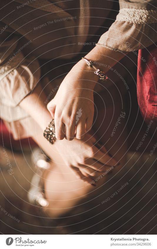 Elegante junge Frauenhände mit bemalten Nägeln und Schmuck Mädchen Eleganz elegant Schönheit Mode Zubehör schön Hände Hand weich rote Couch Porträt Dame