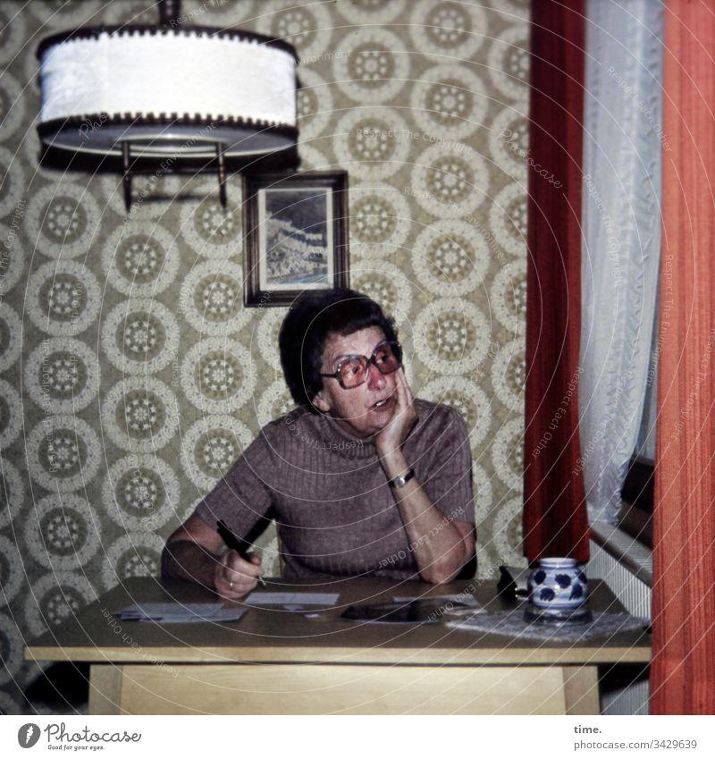 jetzt einen klugen Gedanken ... schreiben wohnzimmer tisch lampe vorhang brief tapete bild nachdenken grübeln überlegen formulieren aufstützen sitzen