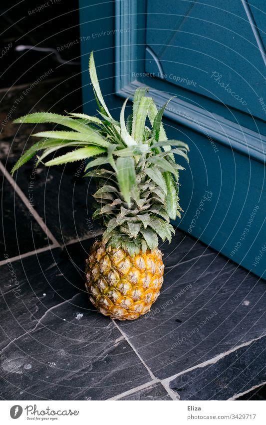 Eine ganze Ananas die auf dem Boden vor einer Tür steht Frucht gesund lecker exotisch blau Geschenk mitbringen grün gelb Ananasblätter Obst frisch Farbfoto süß