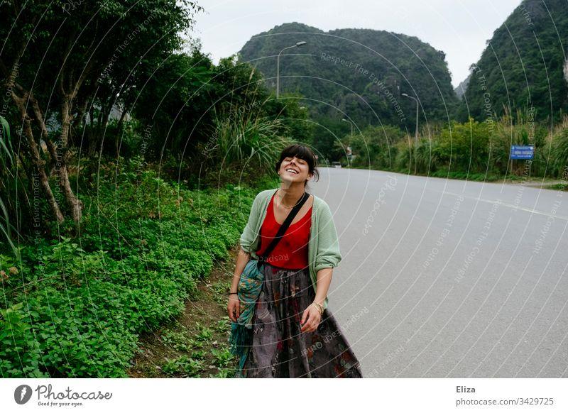 Eine junge Frau in bunter Kleidung, die eine leere Straße in Asien entlangläuft und lächelt Touristin Tourismus Südostasien Lebensfreude Reisen Urlaub
