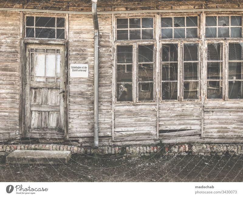 Verfallene und verwitterte Hausfassade Ruine Holz Bretter kaputt zerstört Fassade Zerstörung Wand Fenster Renovieren Vergangenheit Vergänglichkeit Menschenleer