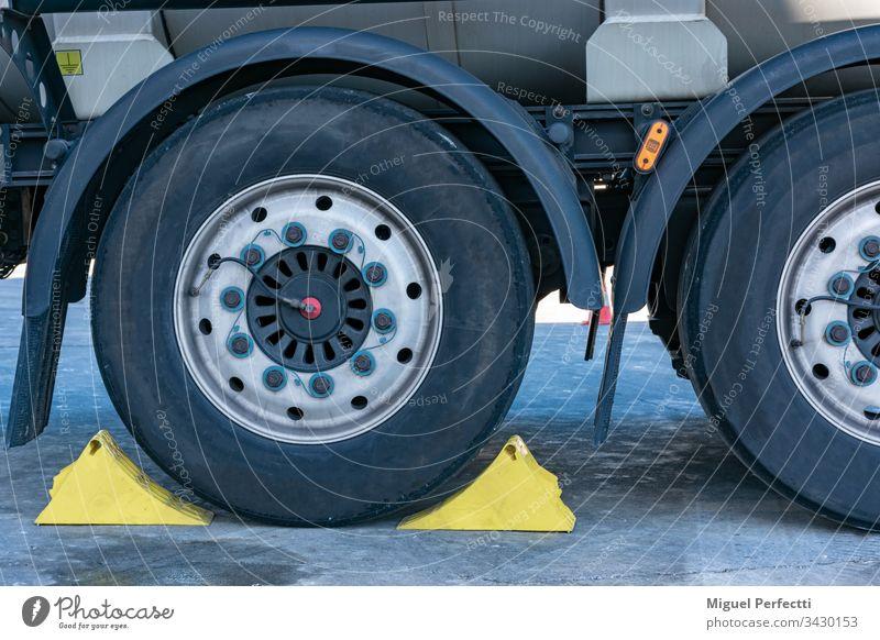 Lkw-Rad mit zwei Unterlegkeilen blockiert Tankwagen halb Auflieger Brechen Verkehr Verkehrssicherheit logistisch Lastkraftwagen Parkplatz Bremsklotz Stahlfelge