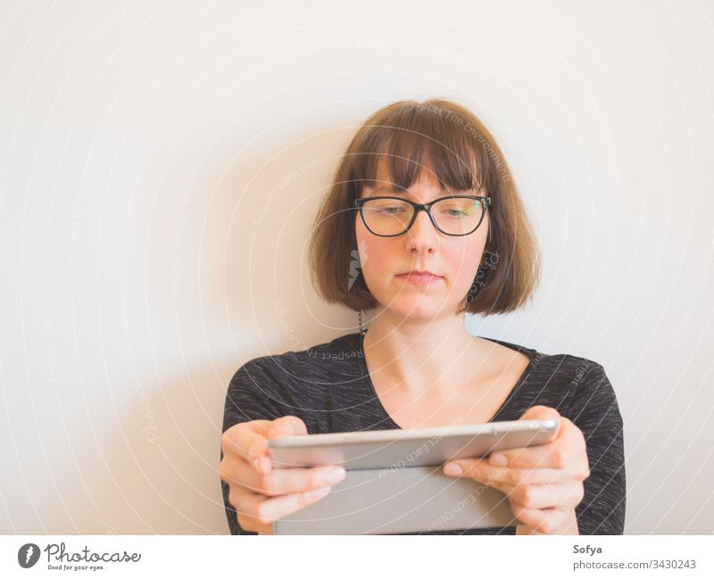 Kaukasische Frau mit Brille, die eine Tablette benutzt benutzend Apparatur Sitzen Kaukasier Porträt Mitte Arbeitswohnung Quarantäne bob horizontal gealtert