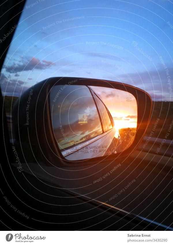 Spiegel eines Autos mit Sonnenuntergang Autospiegel spiegeln PKW farbenfroh Licht Verkehr Straße Autobahn reisen Roadtrip Rückblick Rücken Panorama Landschaft